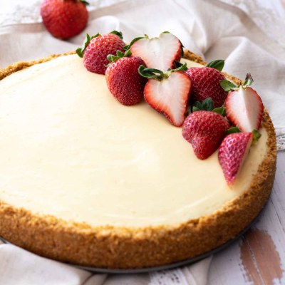 classic cheesecake with fresh strawberries on beige napkin