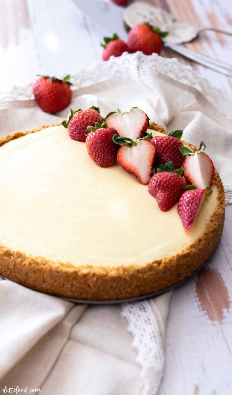classic cheesecake with fresh strawberries on beige napkin