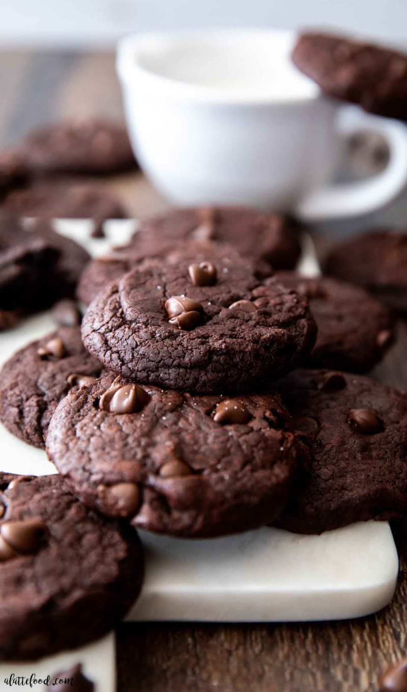 fudge brownie chocolate cookies stacked on white board with glass of milk