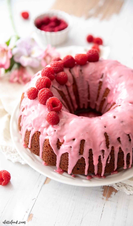raspberry bundt cake with fresh raspberries and pink raspberry glaze on white plate