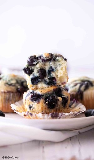 two blueberry muffins made with sour cream and fresh blueberries stacked on top of each other on white plate