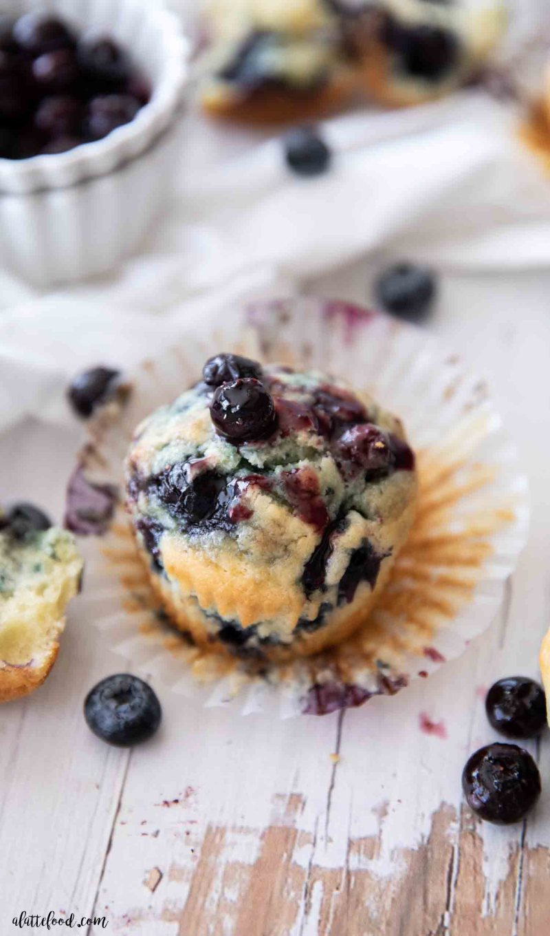 blueberry sour cream muffin with fresh blueberry sauce on white board