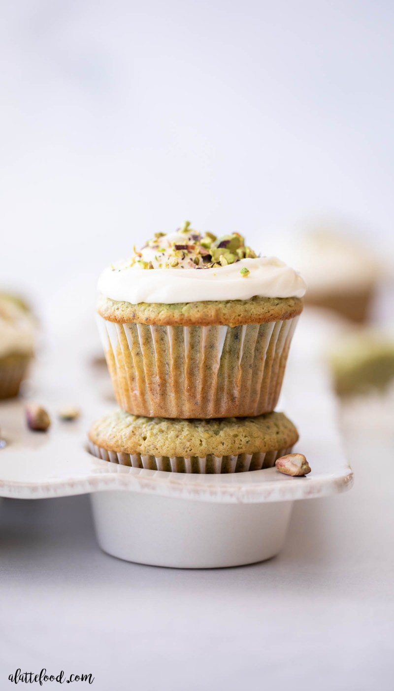 honey pistachio cupcakes with cream cheese frosting stacked on top of each other in white muffin tin