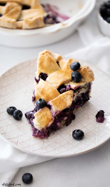slice of lattice blueberry pie on white plate