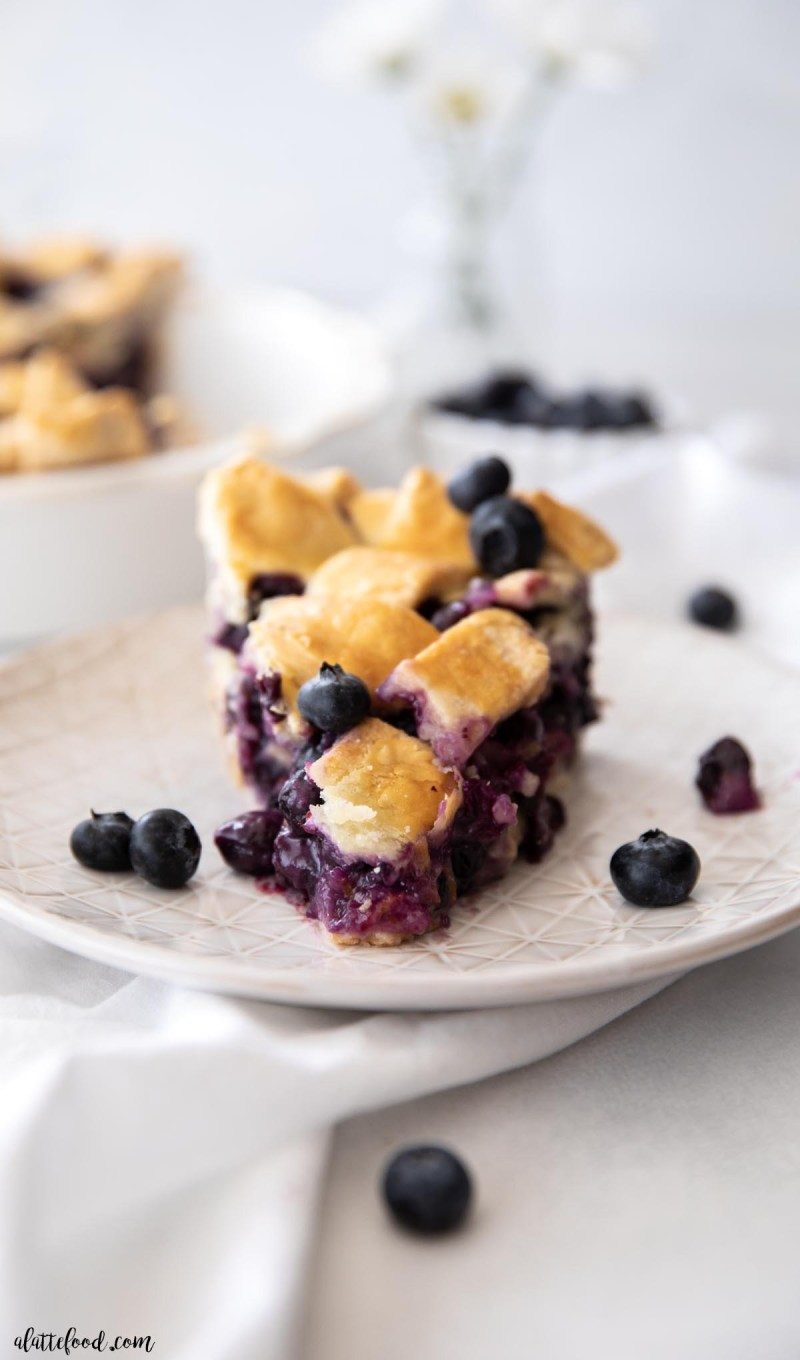 fresh blueberry pie slice with flaky lattice crust on a white plate