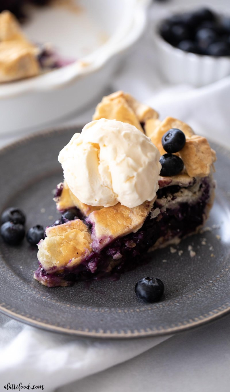 ice cream topped old-fashioned blueberry pie slice on gray plate