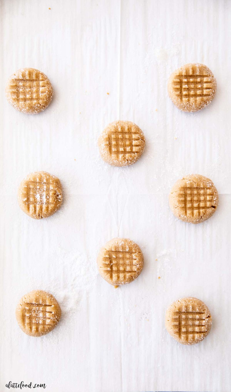 unbaked peanut butter cookies with criss cross pattern on parchment lined baking sheet