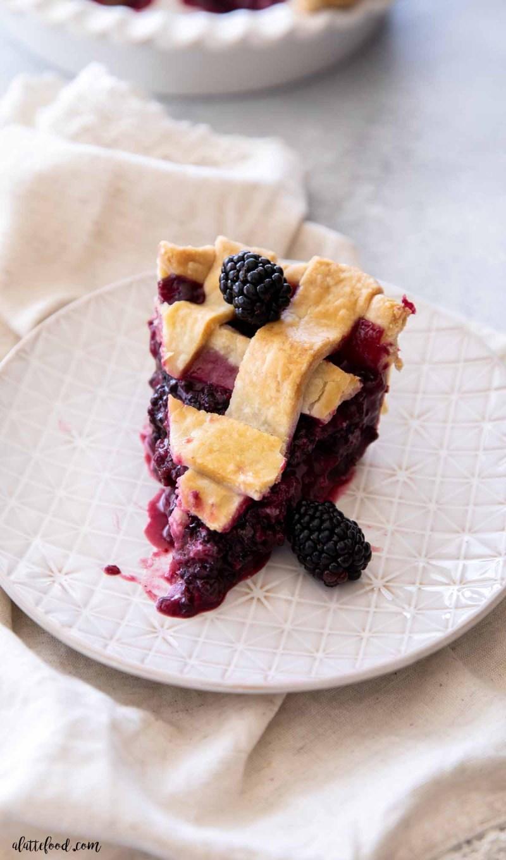 slice of lattice crusted blackberry pie on tan plate