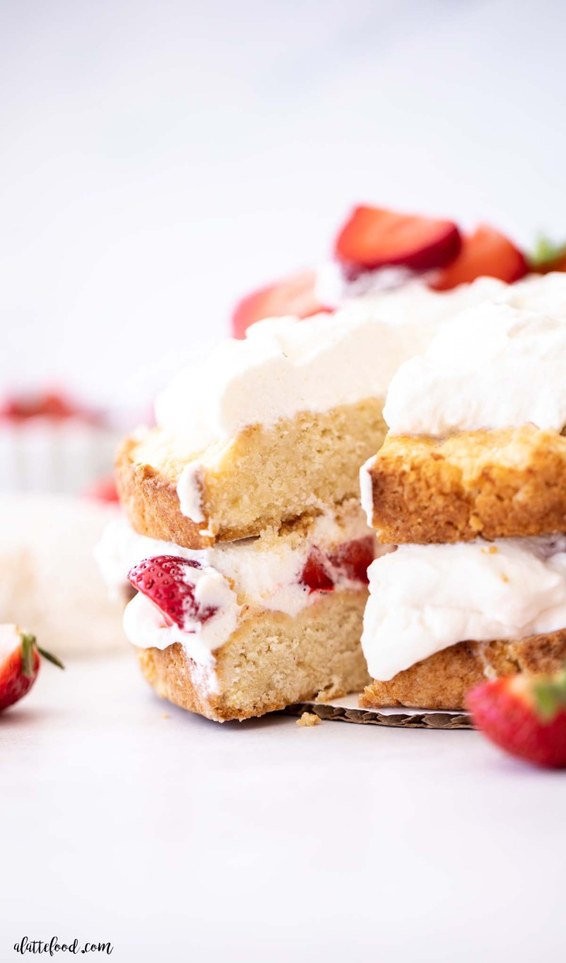 slice of strawberry shortcake layer cake with fresh berries and whipped cream