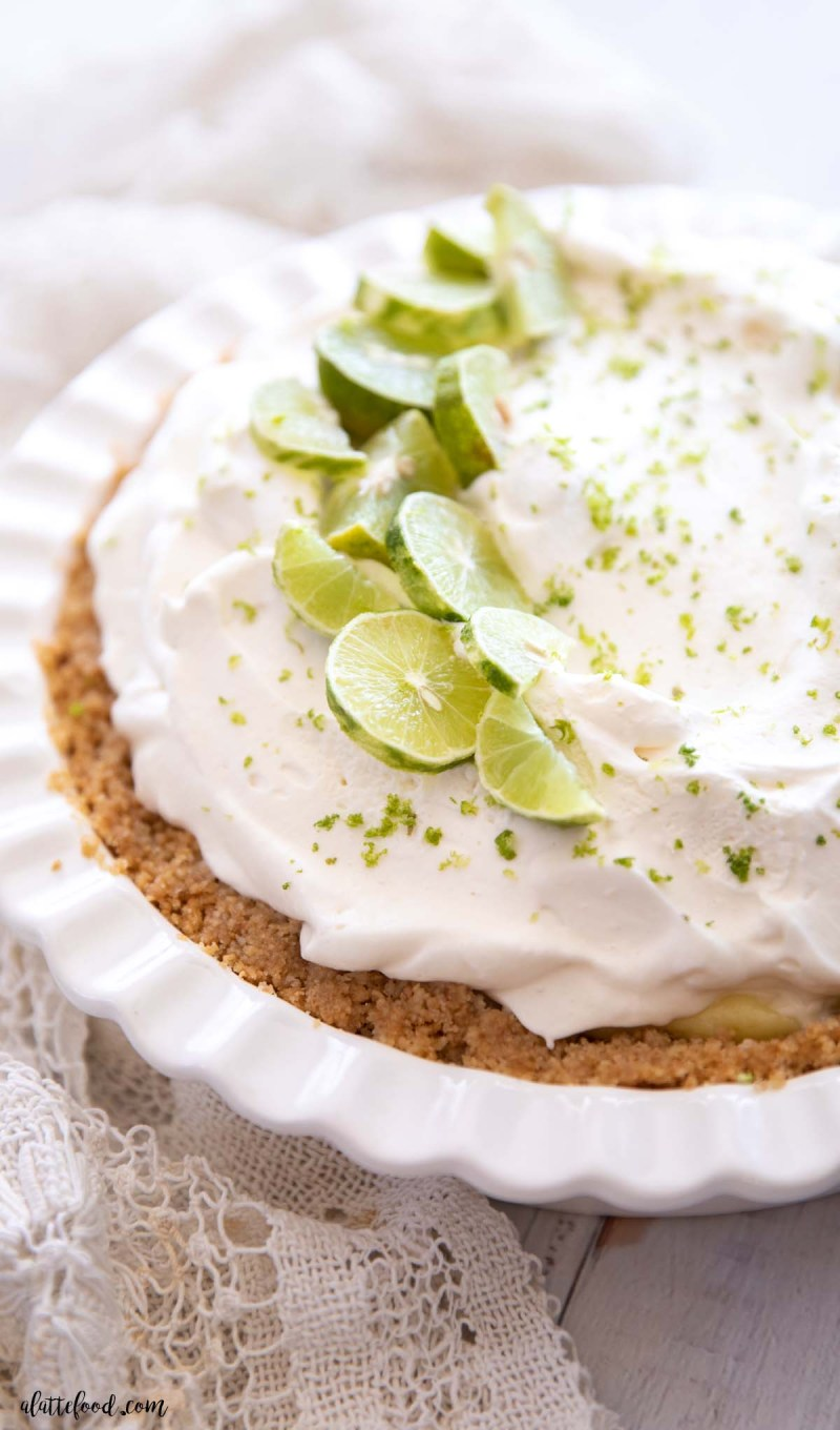 homemade key lime pie with a graham cracker crust in a white pie plate