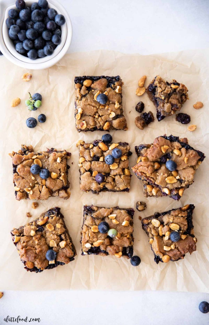 peanut butter cookie bars with blueberry jam cut on brown parchment paper
