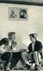 GM045: Two Shala men conversing in Theth, with photos of King Victor Emmanuel III and Mussolini on the wall (Photo: Giuseppe Massani, 1940).