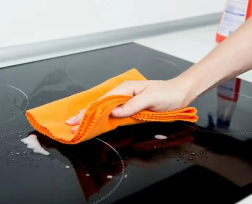 Woman's hand cleaning induction hob with cloth