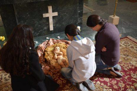 Tres jóvenes refugiadas rezan ante un Pesebre la pasada Navidad.