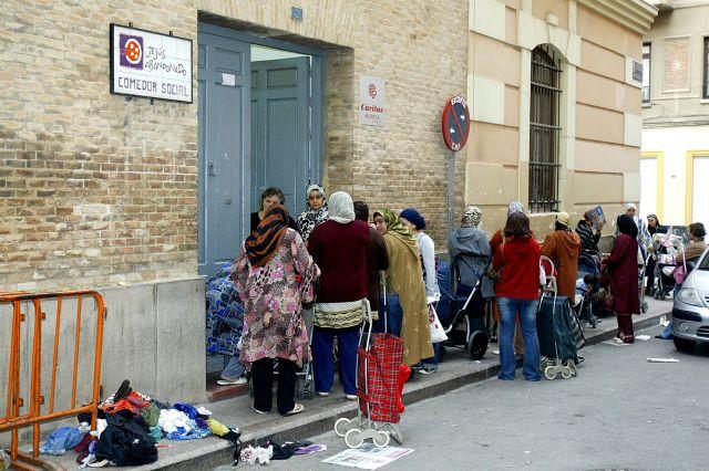 Gratis total: Musulmanas reciben comida en un comedor social.