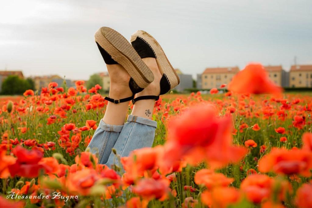 foto creativa di scarpe di ragazza immersa in un campo di fiori