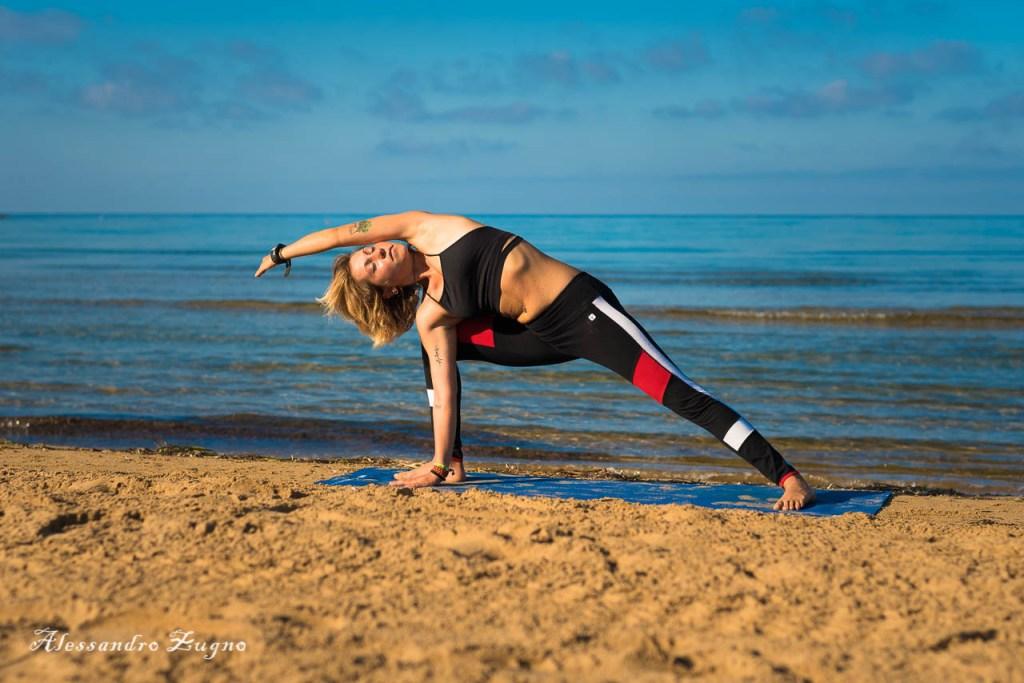foto di Yoga al mare di ragazza nella posizione del guerriero inverso