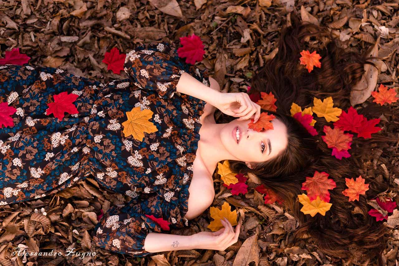 ragazza che posa per Book Fotografico autunnale mentre è immersa nelle foglie