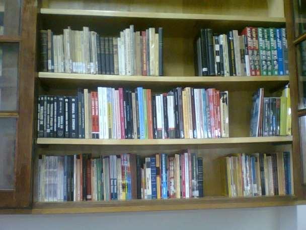 Uma das três estantes de livros da Biblioteca Dijalma Caiafa