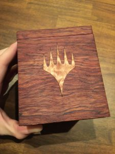 The planeswalker symbol in curly maple inlay