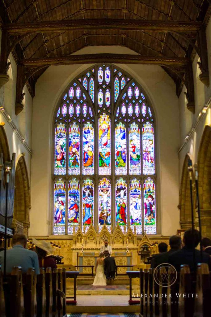 Internal view of Horsham's StMary's Church with the wedding in progress looking at it's large stained glass window