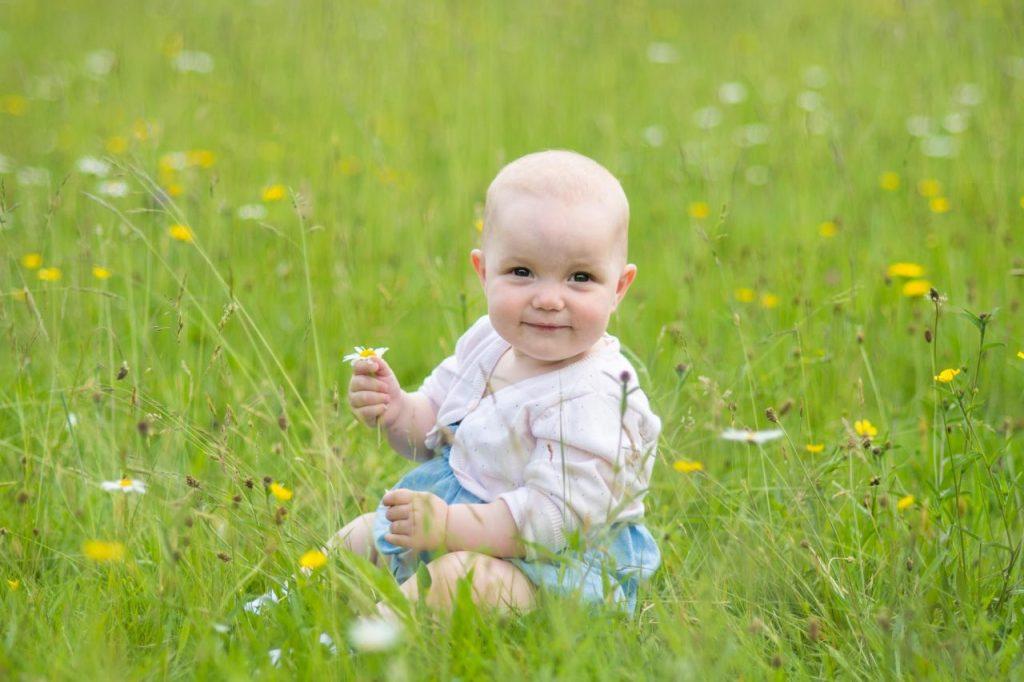 Baby sitting in a field of wild flowers