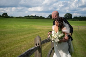wedding photo of the bride and groom looking out over a field