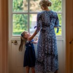 Mother and daughter looking through a door to the garden portrait photo taken at Horsham Registry office