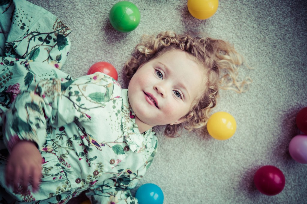 Young girl playing with colourful balls
