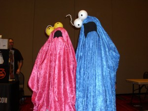 Two people dressed as the yip yip aliens from Sesame Street.