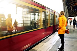 Woman wearing yellow coat, red bag and black kitten heels waits for the train to work.
