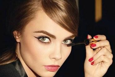 Cara Delevingne applying mascara to eyelashes