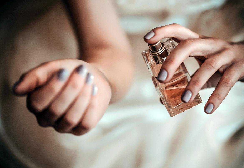 Woman with grey nail varnish sprays perfume onto her wrist