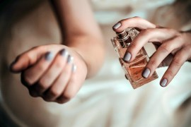 Woman with grey nail varnish sprays perfume onto her wrist