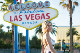 woman wearing black white star sequin jumpsuit in front of las vegas sign