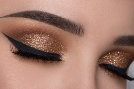 Woman with winged eyeliner and glittery eyeshadow
