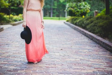 Woman wearing ombre pink maxi dress styled with black hat and sandals