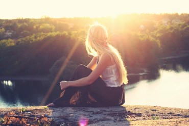 Woman dressed in boho style clothes watches the sunset