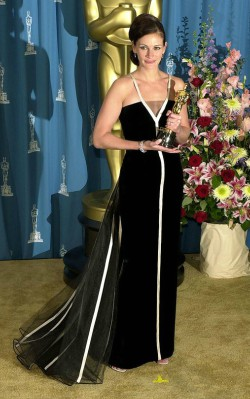 Julia Roberts with her Oscar wearing a strapless black ball gown with white edging