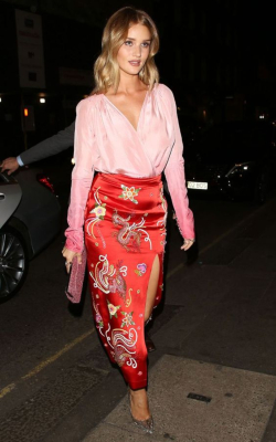 Rosie Huntington Whitley wearing a red print pencil skirt and a pink shirt
