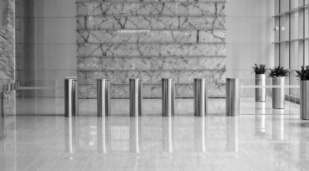 Line of six turnstiles inside building lobby, black and white