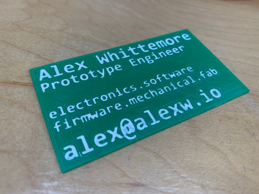 Photo of business card first draft, with bad white paint inlay on green PLA.