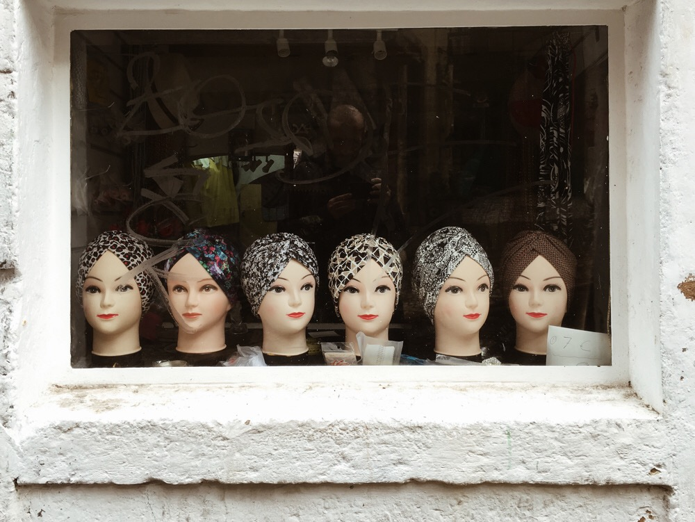 Heads on a window shop by Alfredo Lietor