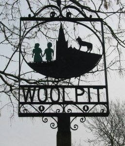 The village sign of Wolpit, England depicting the 2 green children the town is famous for. The sign was erected in 1977.