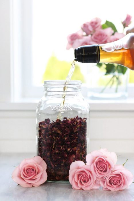 Pouring vinegar into jar full of dried rose petals