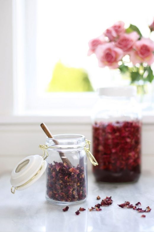 Small pretty jar filled with dried rose petals with jar of rose petal vinegar