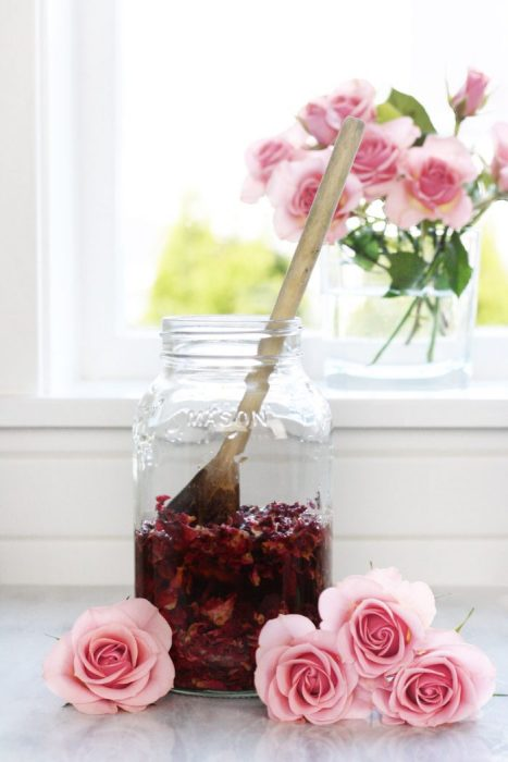 Wooden spoon pushing rose petals into glass jar
