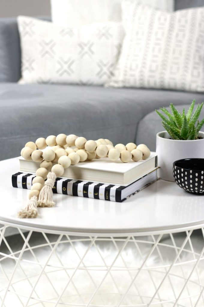 DIY wood bead garland styled on coffee table with mudcloth pillows in background