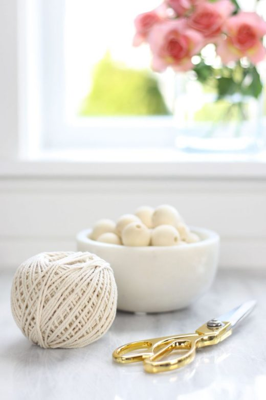 Supplies for making a DIY wood bead garland: cotton twine, gold scissors, and natural wooden beads