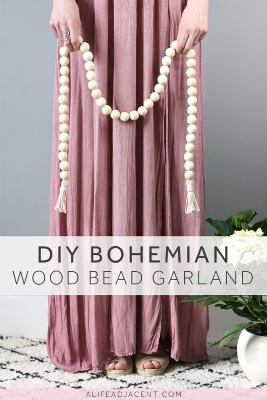 Woman in flowing dress holding DIY bohemian wooden bead garland